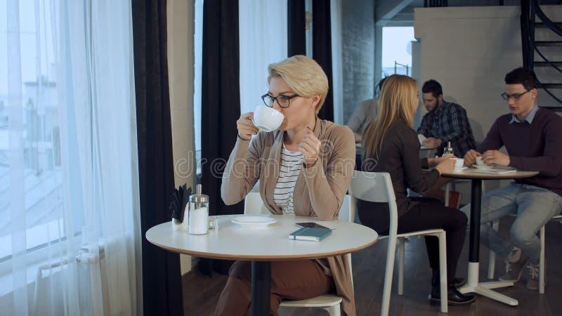 Retrato del té de consumición femenino magnífico joven y cuidadosamente de la mirada fuera de la ventana de la cafetería mientras fotos de archivo