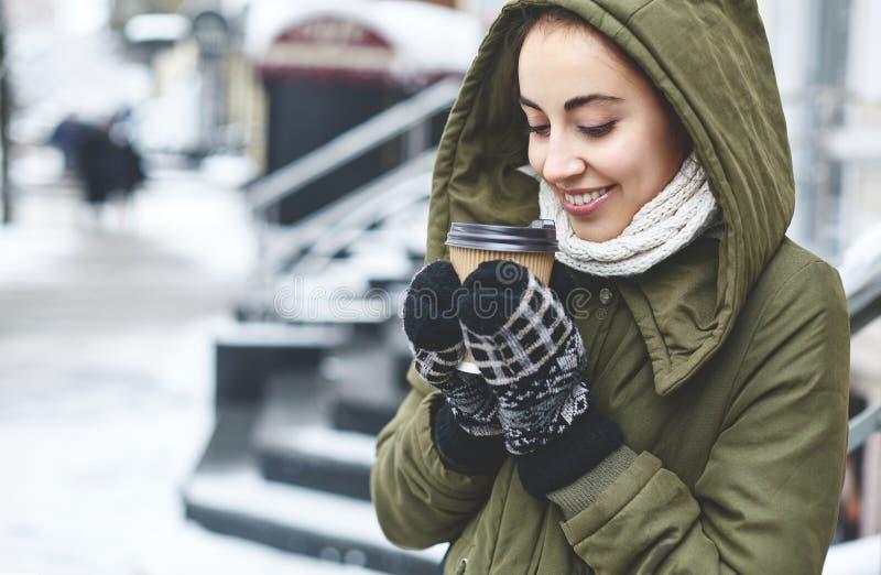 Retrato del té de consumición de la mujer joven al aire libre en la calle del invierno fotos de archivo libres de regalías
