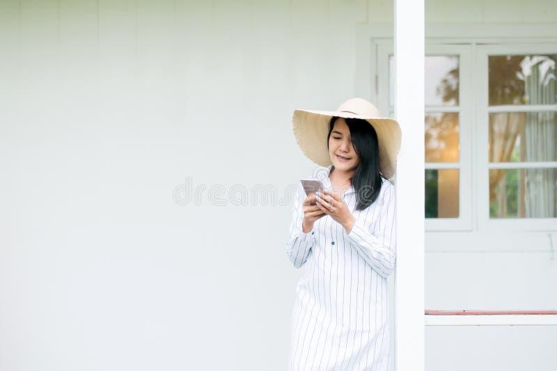 Retrato del tel?fono celular y de la sonrisa que se sostiene femenino asi?tico hermoso en casa, pensamiento positivo, buena actit imagen de archivo