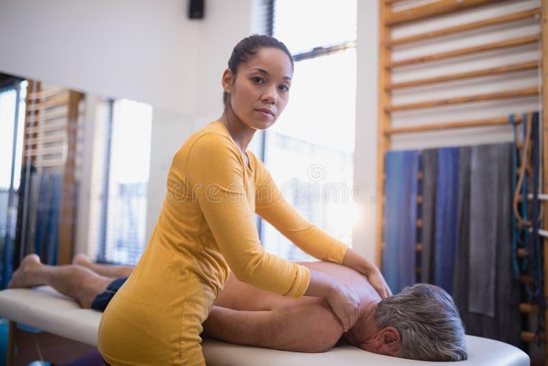 Retrato del terapeuta de sexo femenino que da masaje del cuello al paciente masculino mayor que miente en cama foto de archivo libre de regalías