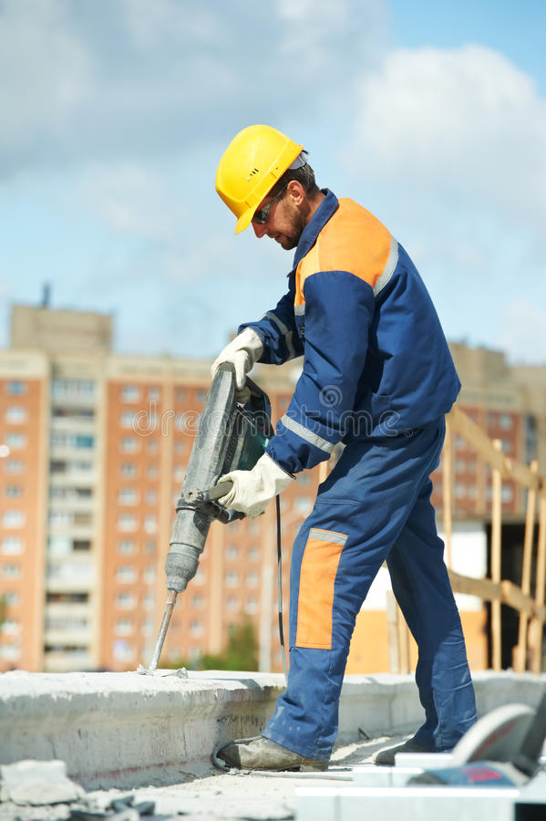 Retrato del trabajador de construcción con el perforador imagenes de archivo