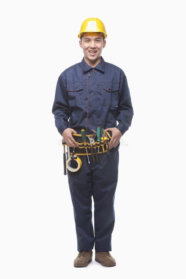 Retrato del trabajador de construcción feliz con la correa de la herramienta, tiro del estudio imagen de archivo libre de regalías
