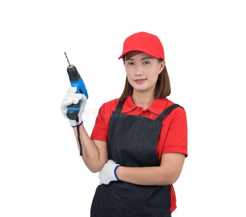 Retrato del trabajador de mujer joven que sonríe en uniforme rojo con el delantal, taladro eléctrico de la tenencia de la mano de imagenes de archivo