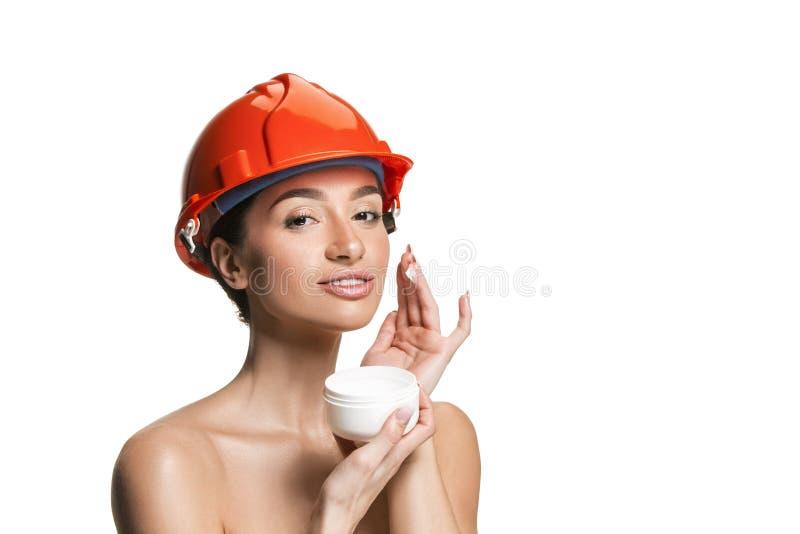 Retrato del trabajador de sexo femenino confiado en casco anaranjado foto de archivo libre de regalías