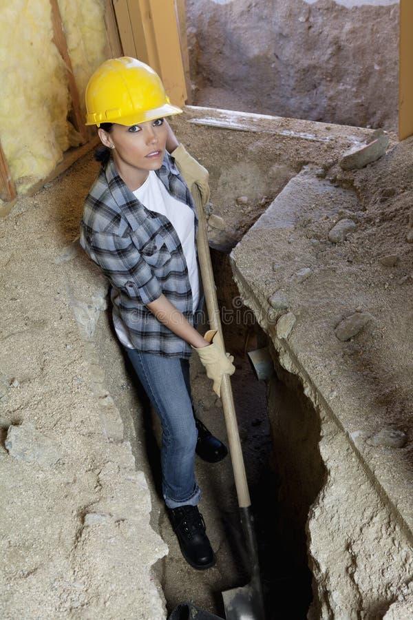 Retrato del trabajador de sexo femenino que cava con la pala en el emplazamiento de la obra fotos de archivo