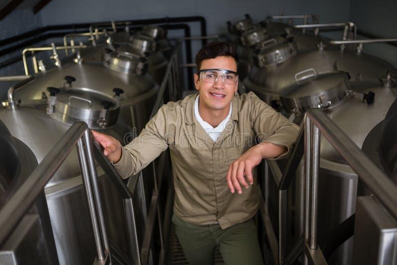 Retrato del trabajador en medio de los tanques de almacenamiento en la cervecería fotos de archivo