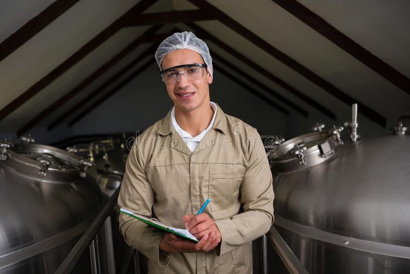 Retrato del trabajador en medio de los tanques de almacenamiento que escribe en el tablero fotografía de archivo libre de regalías