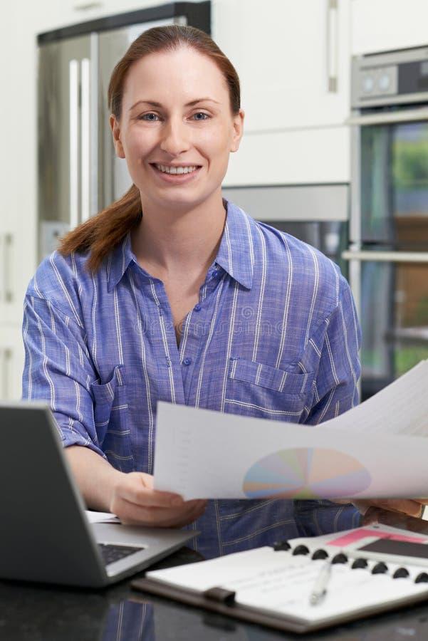 Retrato del trabajador independiente de sexo femenino que usa el ordenador portátil en cocina en H foto de archivo libre de regalías