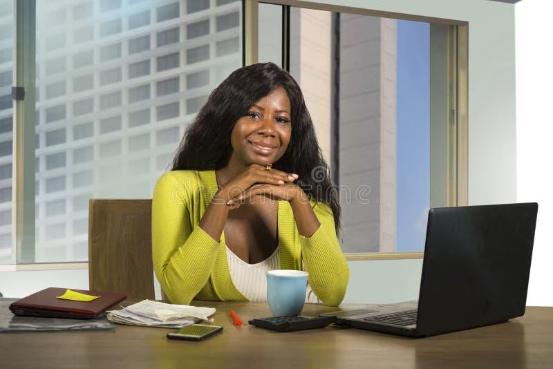 Retrato del trabajo afroamericano negro feliz y hermoso joven de la empresaria confiado en la sonrisa del escritorio del ordenado fotos de archivo
