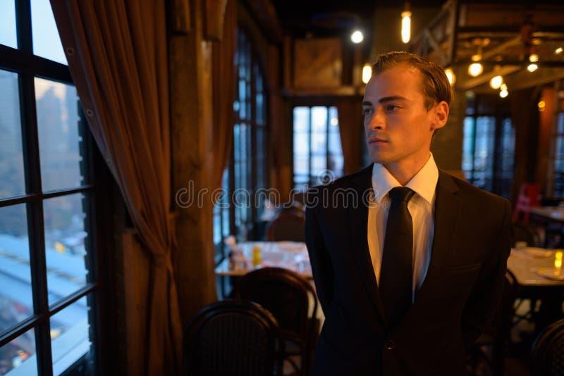 Retrato del traje que lleva del hombre de negocios joven en el restaurante foto de archivo