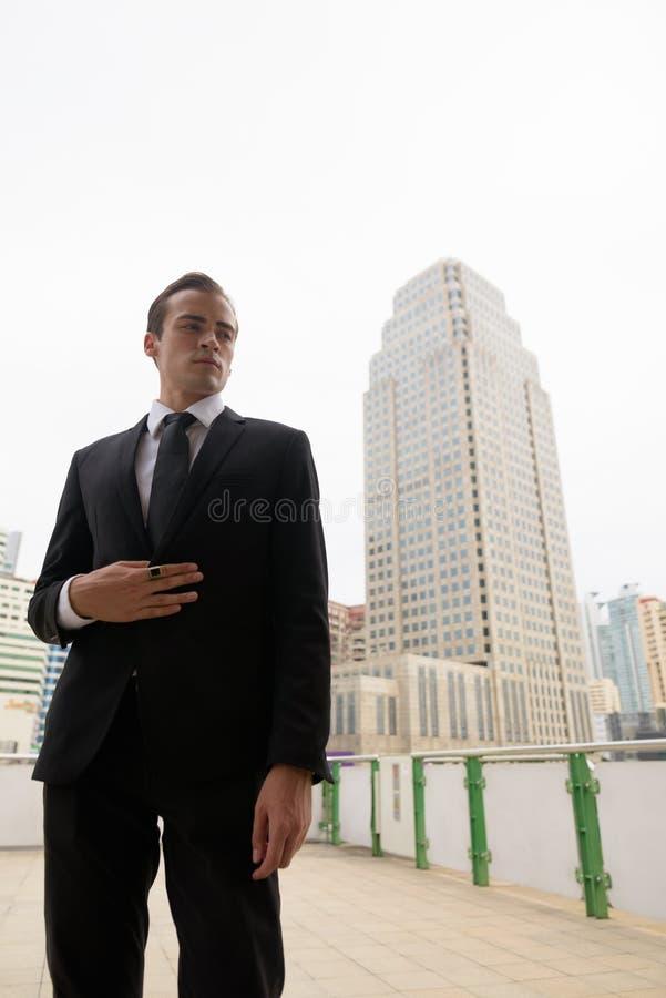 Retrato del traje que lleva y de la colocación del hombre de negocios joven en ciudad fotografía de archivo libre de regalías