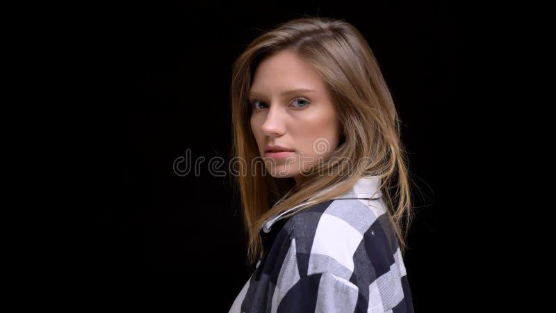Retrato del tres cuartos del primer del caucásico hermoso joven femenino con el pelo marrón que hace una mirada sofisticada en fotografía de archivo