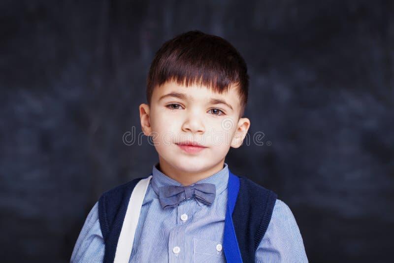 Retrato del uniforme escolar que lleva del muchacho lindo del pequeño niño en fondo negro de la pizarra imagen de archivo libre de regalías