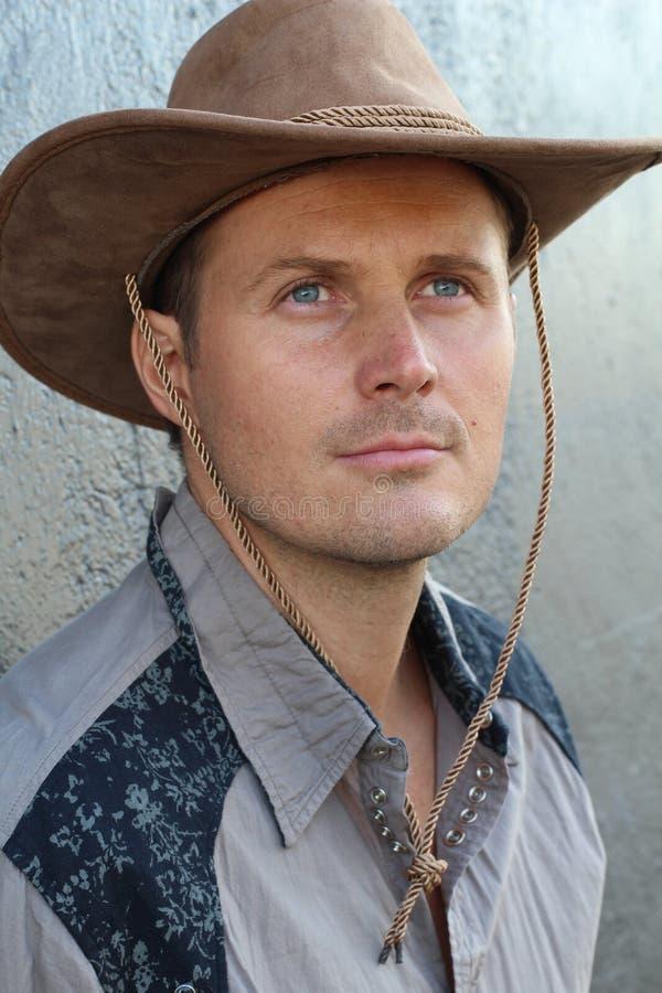 Retrato del vaquero joven serio con el sombrero que parece lejos aislado en fondo gris texturizado imágenes de archivo libres de regalías