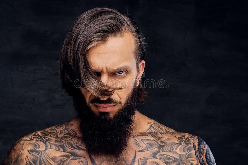 Retrato del varón barbudo descamisado tatuado foto de archivo libre de regalías