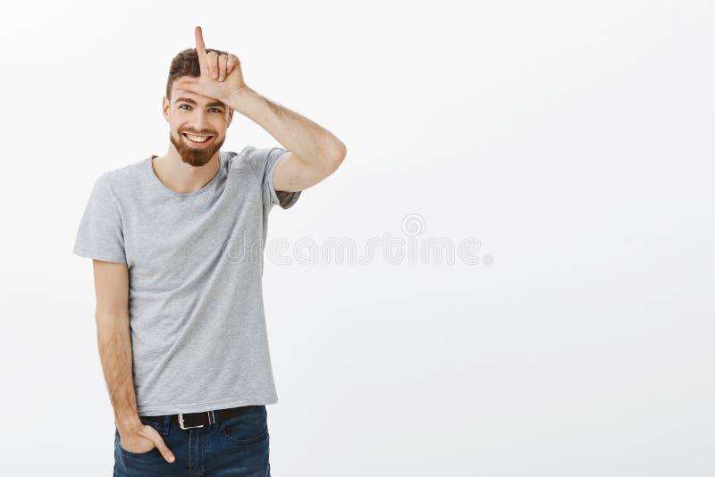 Retrato del varón europeo juguetón y masculino encantador con la barba, los ojos azules y el bigote llevando a cabo la mano en va foto de archivo