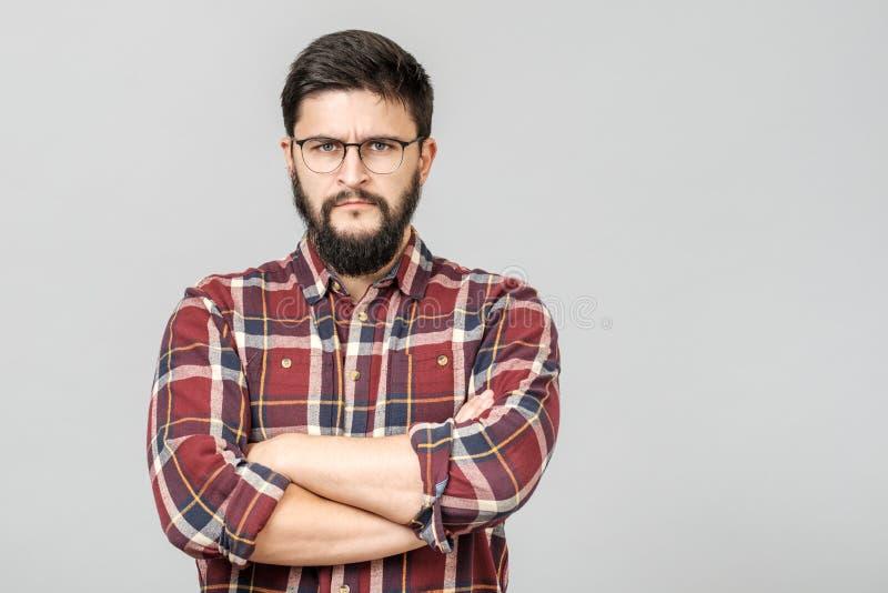 Retrato del varón europeo resuelto infeliz con mirada seria y preocupante contra fondo gris fotografía de archivo libre de regalías