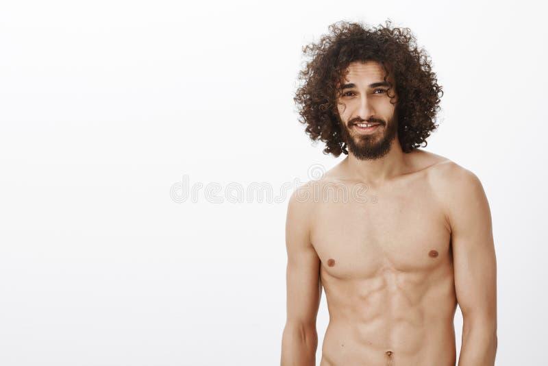 Retrato del varón hermoso confiado masculino con el pelo rizado, colocándose desnudo sobre fondo gris y sonriendo con fotos de archivo libres de regalías
