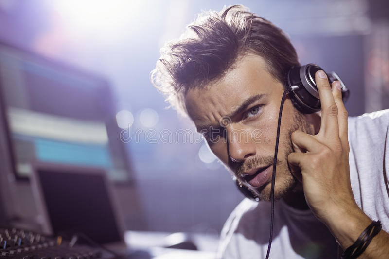 Retrato del varón joven DJ con los auriculares en el club nocturno fotografía de archivo libre de regalías