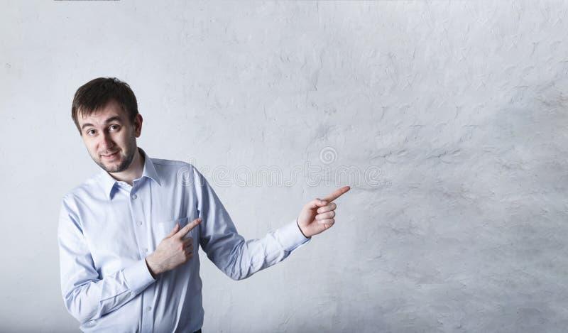 Retrato del varón joven emotivo apuesto que señala izquierda con el dedo índice, queriendo compartir su impresión con los amigos, imagenes de archivo