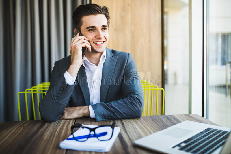 Retrato del varón joven hermoso en los vidrios que se sientan en el escritorio de oficina con el ordenador portátil y que hablan  foto de archivo libre de regalías