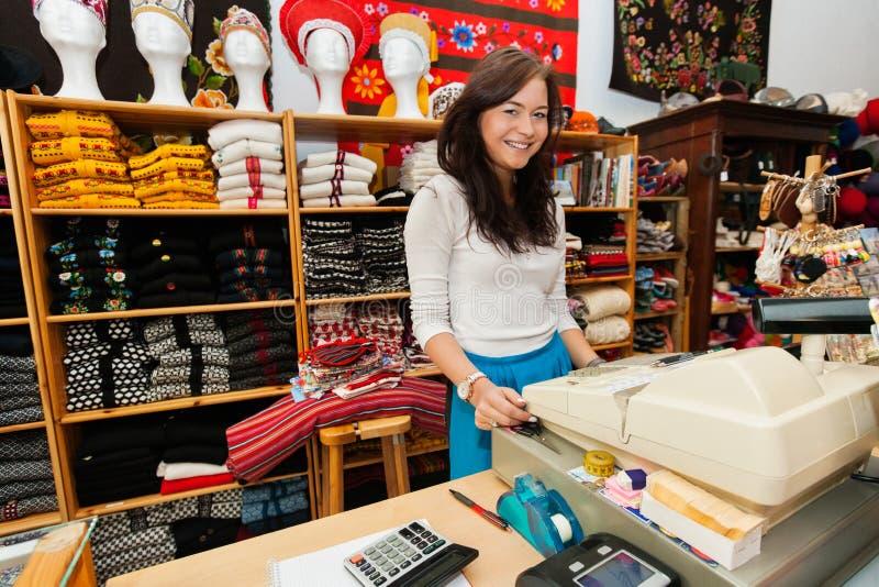Retrato del vendedor de sexo femenino joven sonriente en el soporte del pago y envío en tienda de regalo imagen de archivo