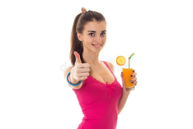 Retrato del verano de la muchacha alegre joven en ropa ligera con el cóctel en la presentación de las manos aislado en el fondo b imágenes de archivo libres de regalías