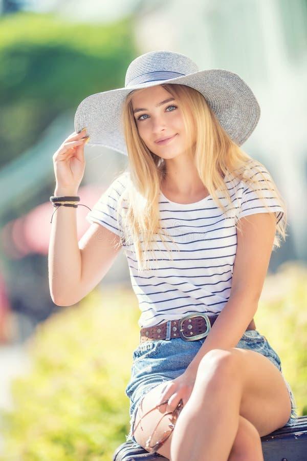 Retrato del verano de la mujer hermosa joven en el sombrero que se sienta en banco en parque imagen de archivo libre de regalías