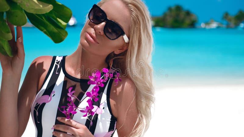 Retrato del verano de la mujer rubia atractiva en gafas de sol de moda con las flores p?rpuras que broncea en la playa tropical P fotografía de archivo libre de regalías