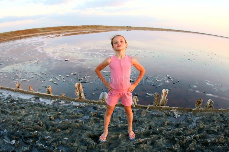 Retrato del verano de un primer de la muchacha, en un lago de sal en la puesta del sol, la muchacha con las caras contentas y jug imagen de archivo