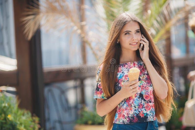 Retrato del verano de una muchacha con helado, hablando en el teléfono imagenes de archivo