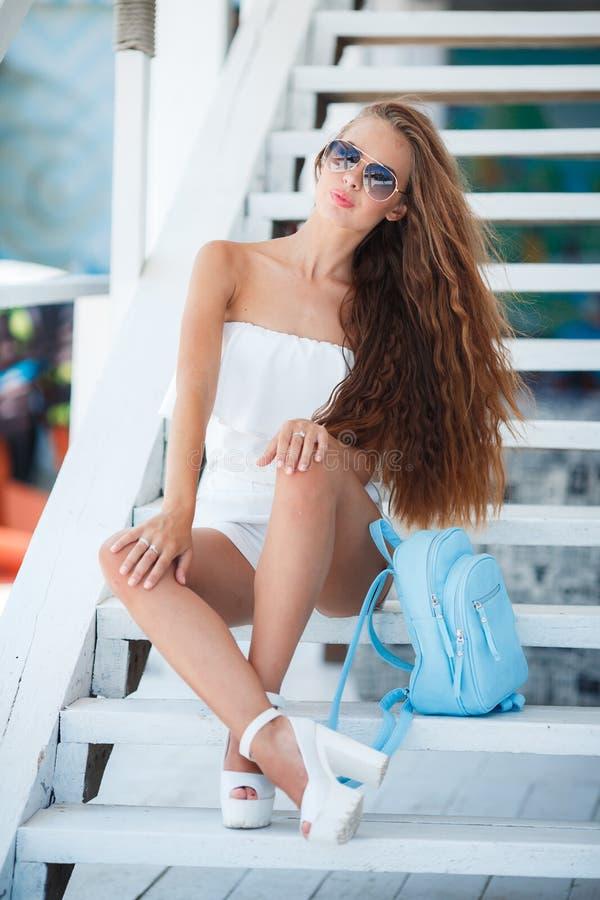 Retrato del verano de una mujer hermosa en los pasos blancos fotografía de archivo