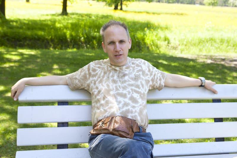 Retrato del verano del hombre maduro en un banco en el parque fotos de archivo