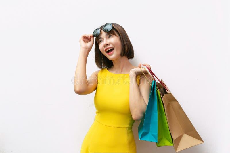 Retrato del vestido que lleva y de las gafas de sol de la muchacha hermosa que sostienen bolsos de compras imagenes de archivo