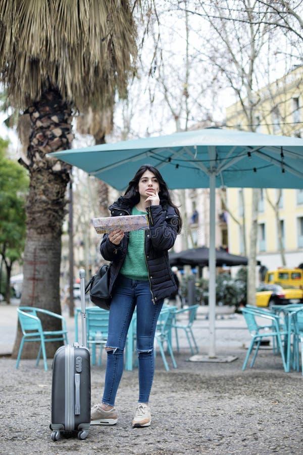 Retrato del viajero casual hermoso feliz de la mujer que busca la dirección en mapa de ubicación foto de archivo