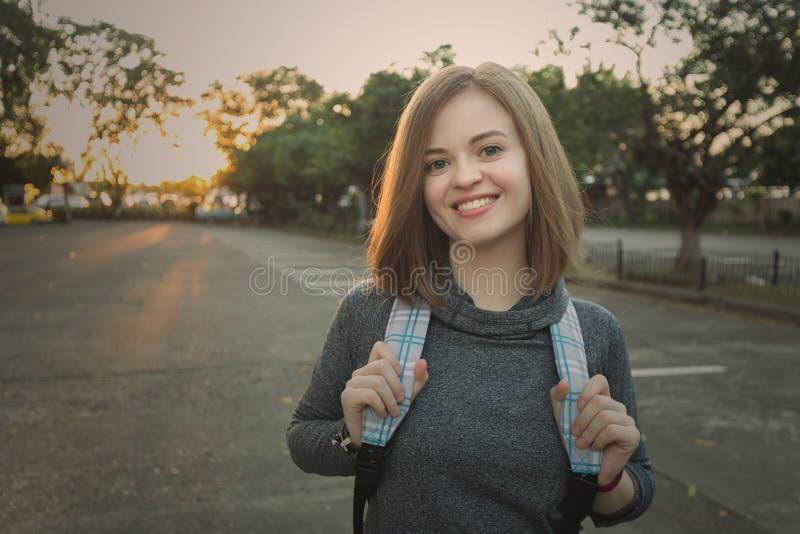 Retrato del viajero caucásico sonriente joven de la mujer con la mochila imagen de archivo