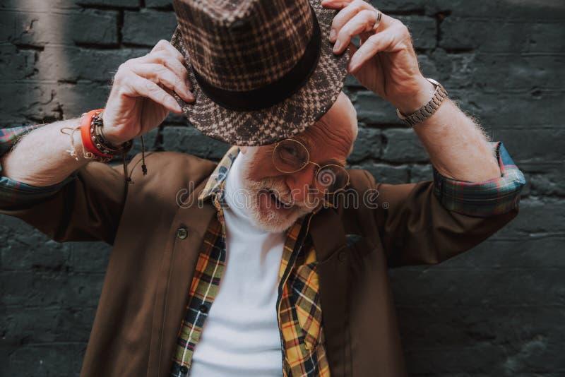 Retrato del viejo hombre alegre que mira a escondidas hacia fuera su sombrero fotografía de archivo