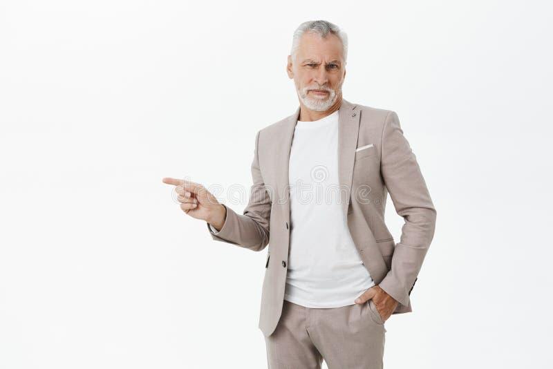 Retrato del viejo hombre barbudo rico descontentado mandón en mano de la tenencia del traje en bolsillo que señala la aversión de fotografía de archivo