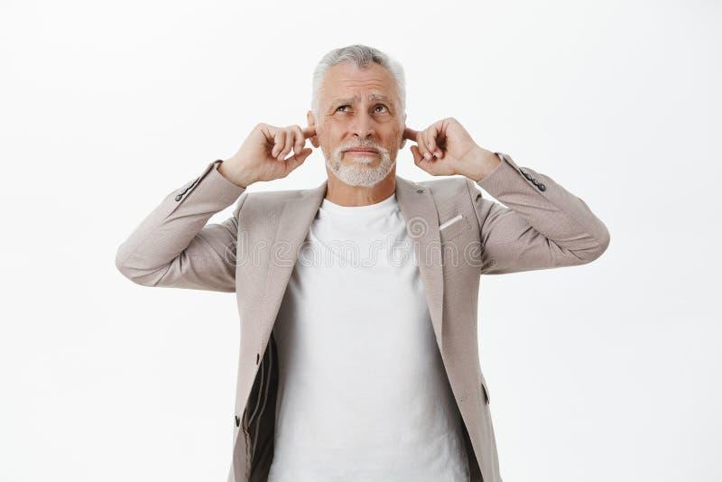 Retrato del viejo hombre de negocios que es perturbado por los oídos cerrados ascendentes que vienen del fuerte ruido con los ded fotografía de archivo