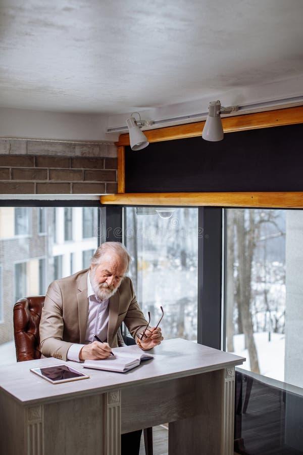 Retrato del viejo hombre de negocios que sostiene sus vidrios y que escribe sus ideas foto de archivo