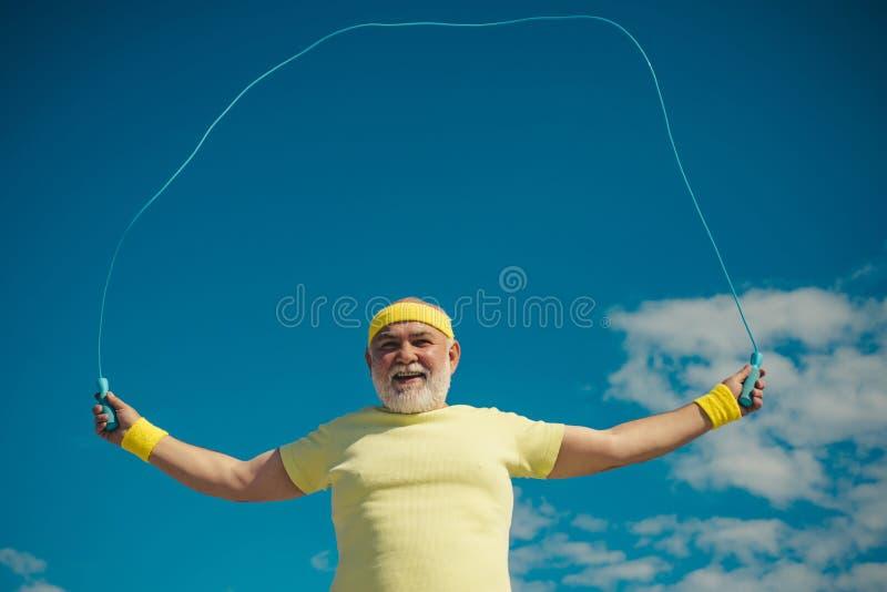 Retrato del viejo hombre que ejercita con la cuerda de salto en fondo del cielo azul Concepto del retiro de la libertad Retrato d fotografía de archivo libre de regalías