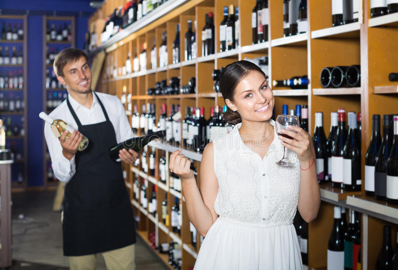 Retrato del vino femenino alegre de la prueba del cliente antes de comprar fotografía de archivo libre de regalías