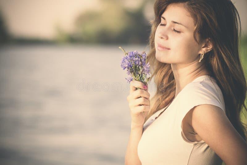 Retrato del vintage de una mujer joven hermosa con un ramo de wildflowers a disposición en los bancos del río por la mañana fotografía de archivo libre de regalías