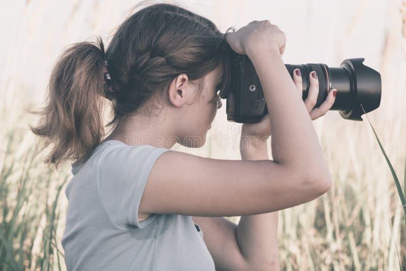 Retrato del vintage de una mujer joven hermosa que le gusta tomar imágenes de la naturaleza foto de archivo libre de regalías
