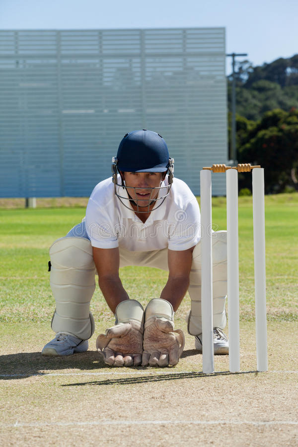 Retrato del wicketkeeper que se agacha detrás de tocones en campo imagen de archivo