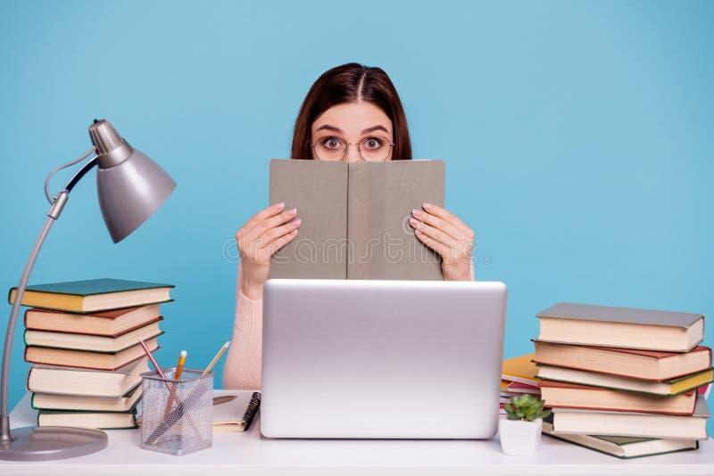 Retrato dela ela queolha a menina diligente assustado receosa atrativa que esconde atrás do livro científico no lugar de trabalho imagens de stock royalty free