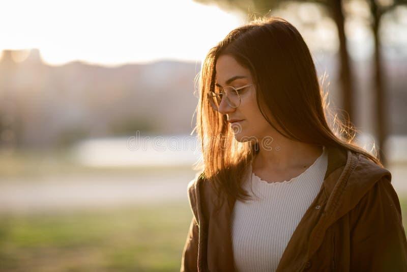 Retrato delantero de la mujer hermosa en un parque durante puesta del sol fotografía de archivo