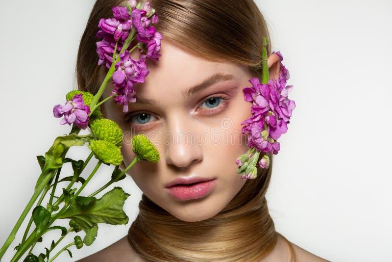 Retrato delicado da beleza de mola de uma menina bonita com o pesco?o envolvido em seus cabelo, flores roxas perto de sua cara e imagem de stock royalty free