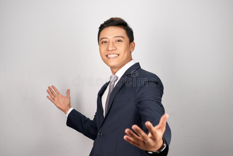 Retrato disparado do homem de negócios novo alegre com os braços abertos e o sorriso da propagação ao estar no fundo branco imagem de stock royalty free
