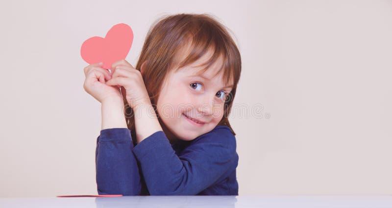 Retrato divertido de la muchacha linda del pequeño niño con el corazón rojo como símbolo del amor y del amorousness fotos de archivo libres de regalías